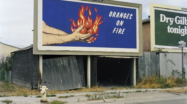 "A color photograph of a large blue and orange billboard with the words ""oranges on fire"", Mandel Sultan"