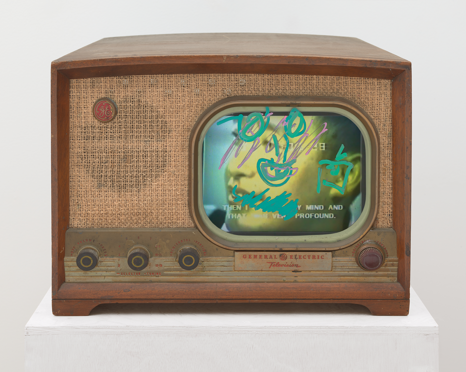 Old-fashioned General Electric television with a screen showing color video painted over with opaque neon scribbles