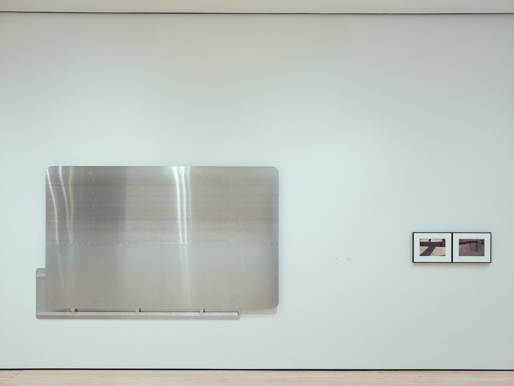 A hung panel of brushed aluminum next to two smaller framed photographs of picnic benches