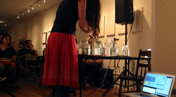 A woman wearing a red skirt bends over a table filled with glasses, Gallardo