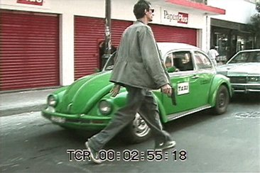 Als, man holding gun walking in front of green taxi