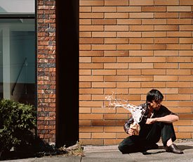 Jeff Wall; man sitting in front of brick wall holding spilling beverage