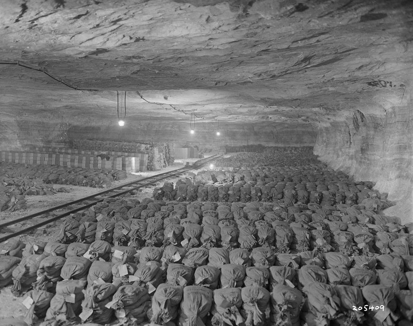 Black and white photograph of wrapped artworks lined up in a cavern