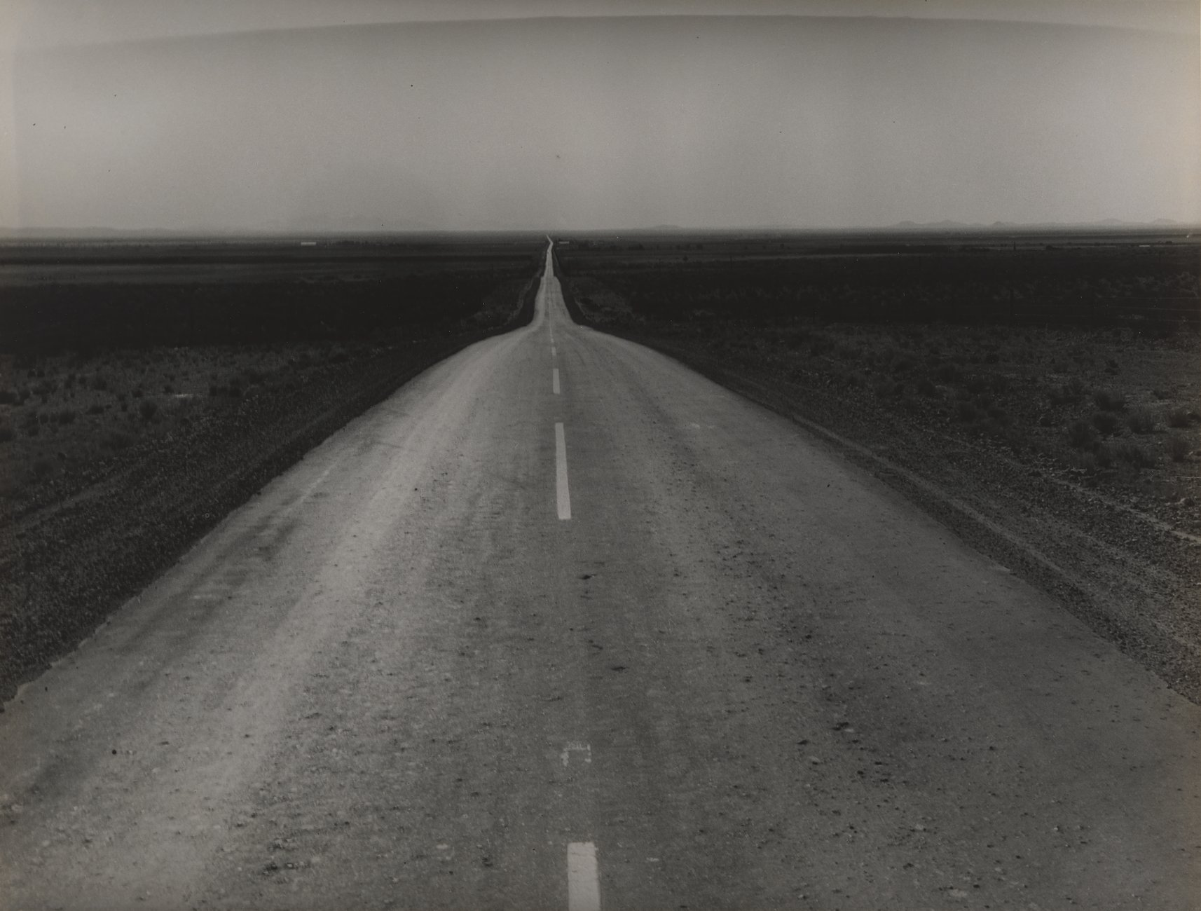 Black and white photograph of empty two-lane highway receding into the flat horizon with a cloudless sky above