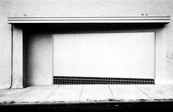 Lewis Baltz, black and white photo of sidewalk and street wall