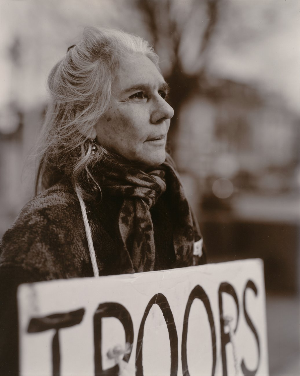 "A black and white portrait of a woman with white hair holding a protest sign reading ""Troops"
