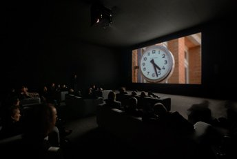 crowd of people sitting in room watching projection with image of clock