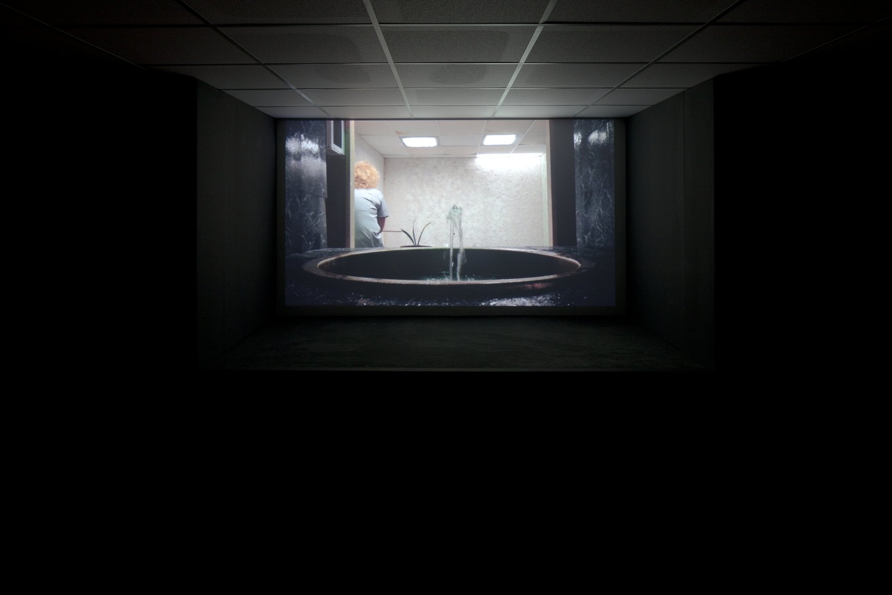 A projection of a fountain with a person in the background