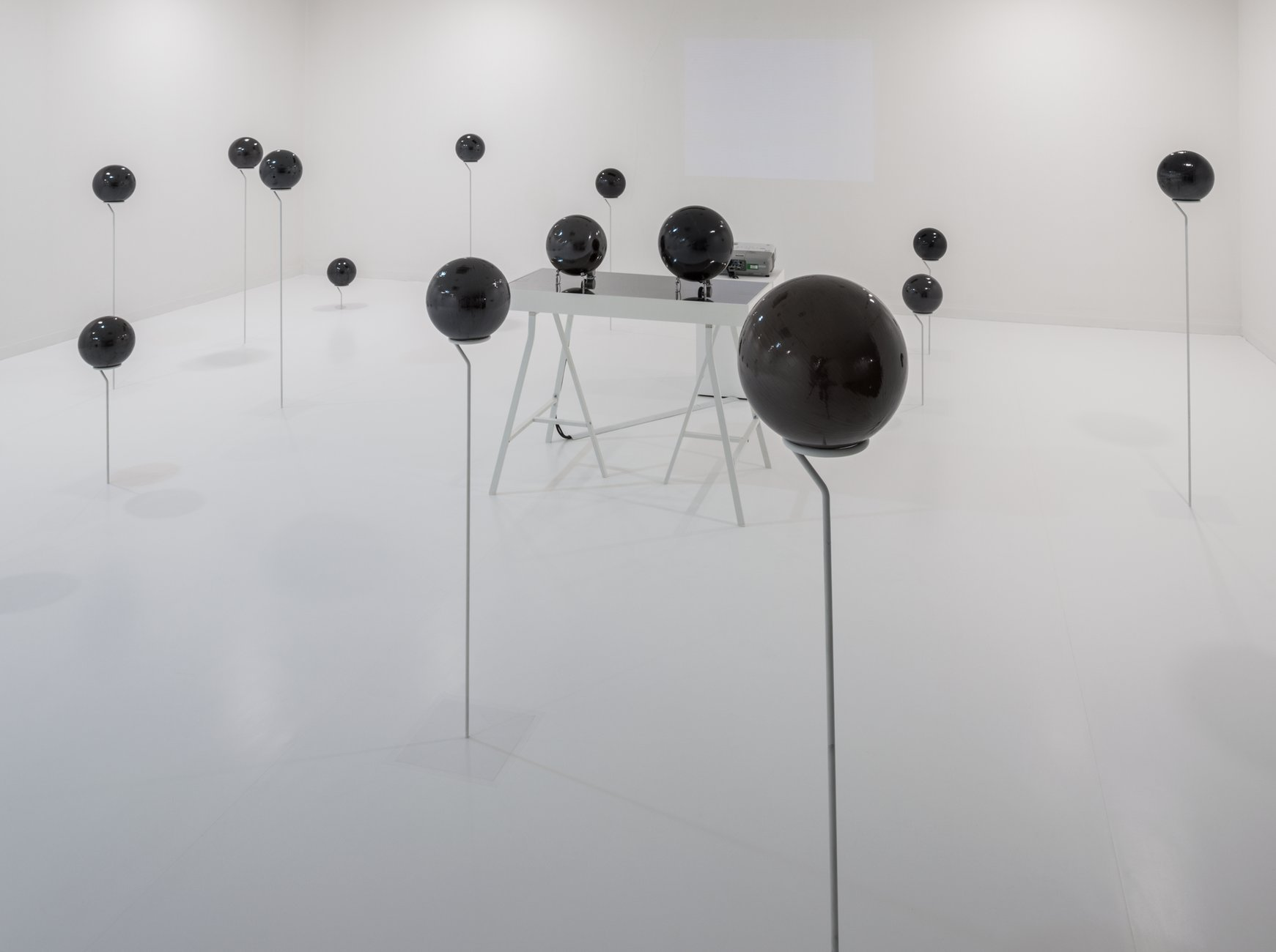 A white room filled with dark spheres mounted on sticks, Yagi Soundtrakcs