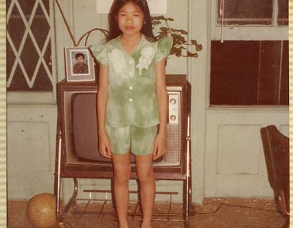 An old color photograph shows an Asian girl standing in a green outfit before at TV