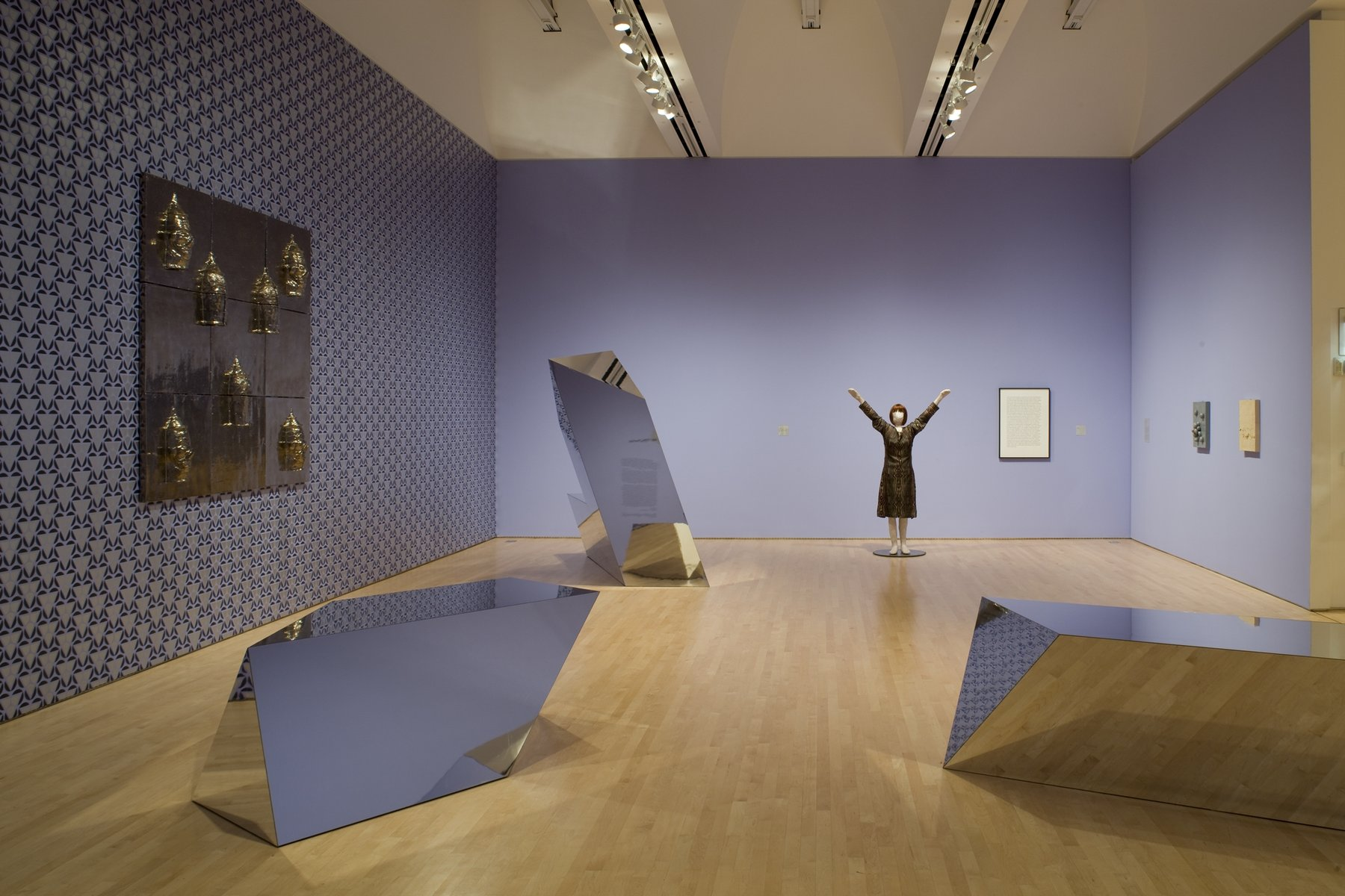 A sculpture of a woman with her hands raised in the air next to a framed block of text, three wall-hanging sculptures, and three reflective geometric sculptures