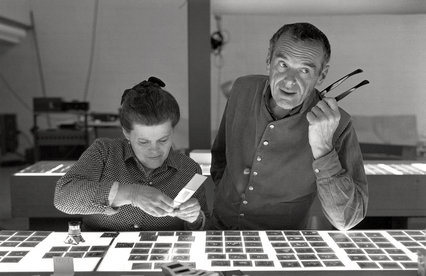 A black and white photograph of a Caucasian man and women standing over a lightbox, ECR, Eames, Designed in CA