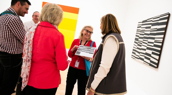 A museum guide speaks to a group of visitors
