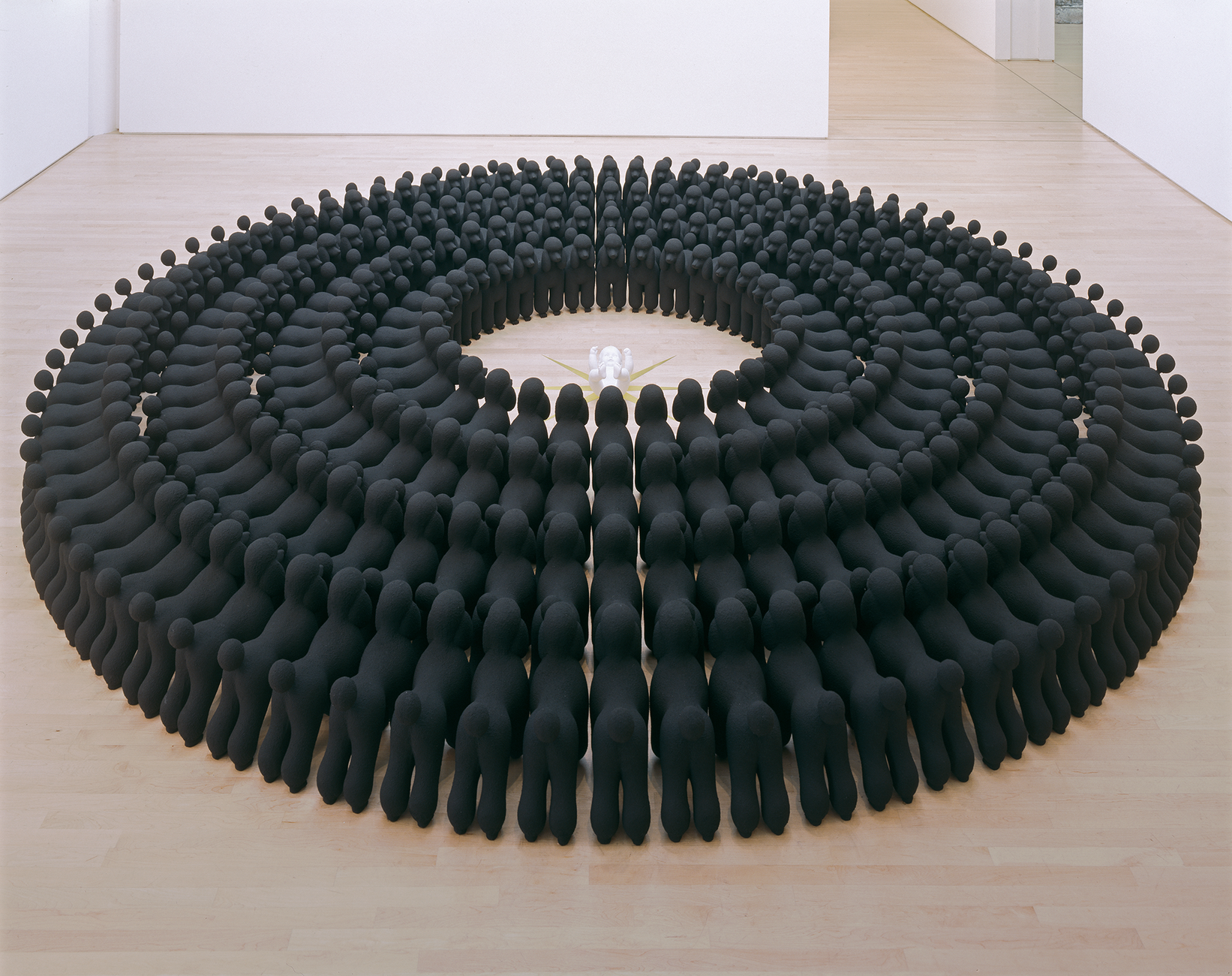 Concentric circles of black poodle sculptures, facing inward, surrounding a white baby figure lying on a gold star