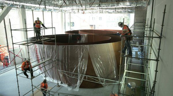 Construction workers in hard hats on scaffolding install large Richard Serra work