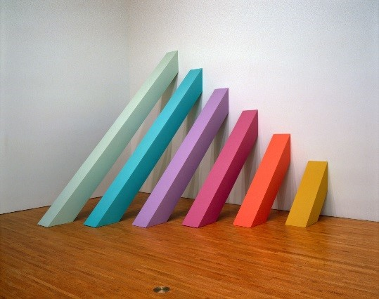 A sculpture featuring colored blocks leaning up against a wall to form a rainbow