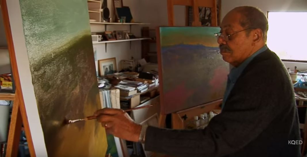 A video still showing an African American man painting, Mayhew