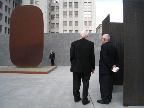 Ellsworth Kelly standing at right, with his 1973 sculpture _Stele I_at the left, and standing with Senior Curator of Painting and Sculpture Gary Garrels, beside Barnett Newman's _Zim Zum_ (1969).