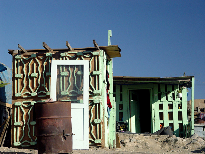 Ingrid Hernández, Tijuana Comprimida, Tijuana 2004. Ingrid Hernández takes photos of the homes of Tijuana's working poor. Many are made from refuse from US factories, highlighting the complicated relationships between the United States and Mexico at the border.