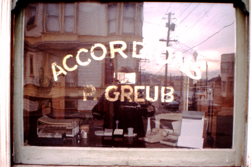 Front window, with gold leaf sign left by Paul Greup, the Swiss accordion maker who previously own 500 Capp Street; photo: David Ireland; image courtesy of The 500 Capp Street Foundation.