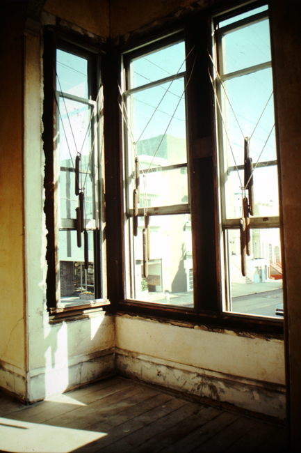 Front parlor room windows with trim removed and arrangement of weights, 1977; photo: David Ireland; image courtesy of The 500 Capp Street Foundation.