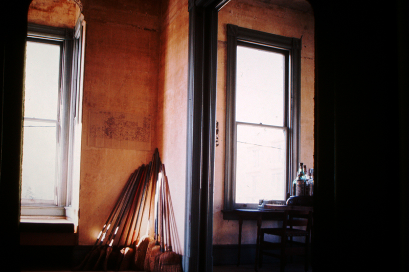 Brooms found in every corner of every room inside 500 Capp Street, leaning against the back parlor room wall, c.1976; photo: David Ireland; image courtesy of The 500 Capp Street Foundation.