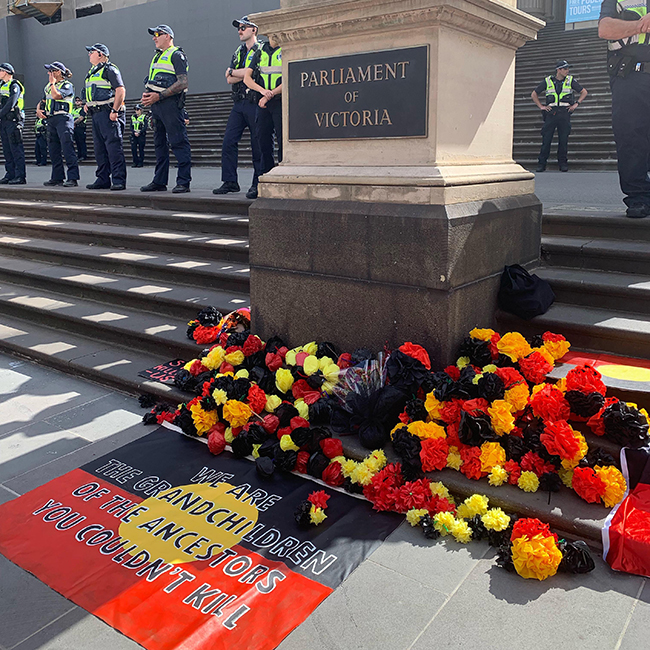 A tribute on the steps of Parliament House, surrounded by cops, January 26 2019.