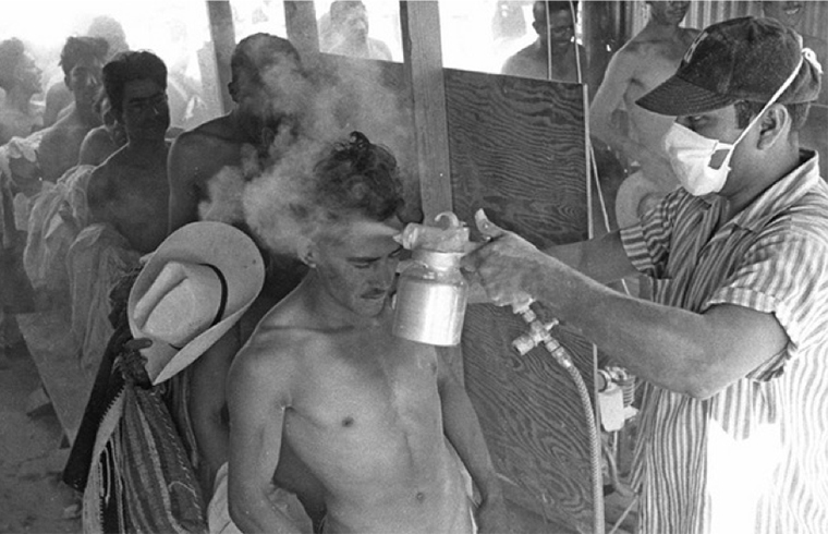 A Bracero being fumigated with DDT. Leonard Nadel, El Paso, Texas, 1956. Collection of National Museum of American History.