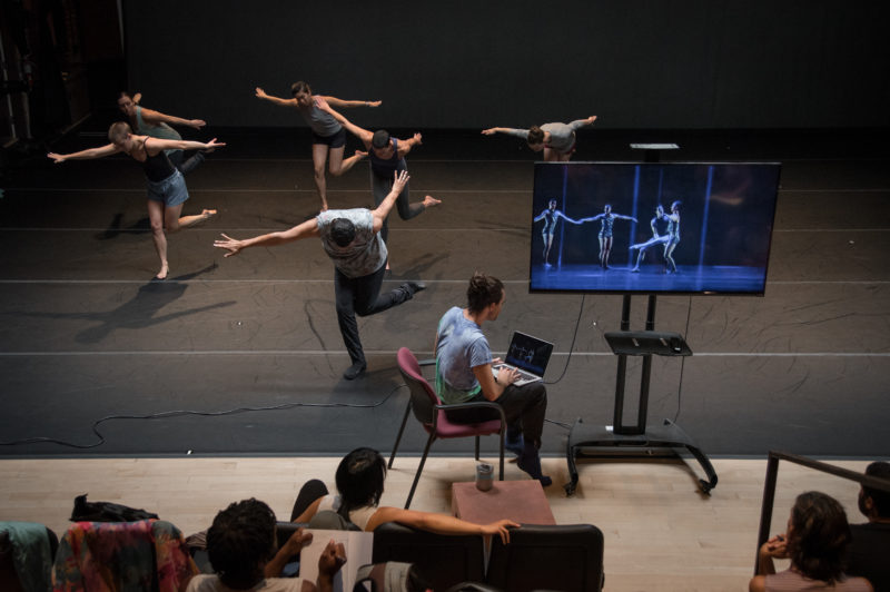 Rashaun Mitchell teaching repertory to the dancers while Silas Riener shares footage with the commissioned artists. Photo: Hillary Goidell.