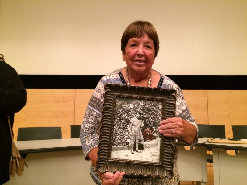 Ruth Orta holding a framed photograph of her mother, after the panel.