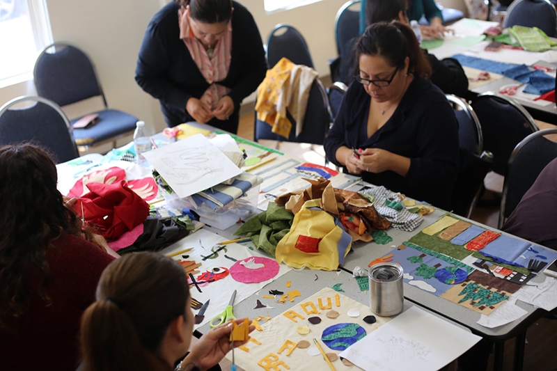 Women from the Latina Center's Leadership group participate in a social justice quilt workshop, 2018. In August 2018 the Richmond Art Center and Social Justice Sewing Academy partnered to run a workshop at The Latina Center in Richmond. Women from the leadership program learned how to visualize social justice issues to design a quilt. This quilt was included in an exhibition at the Richmond Art Center, Empowering Threads, in winter 2019.