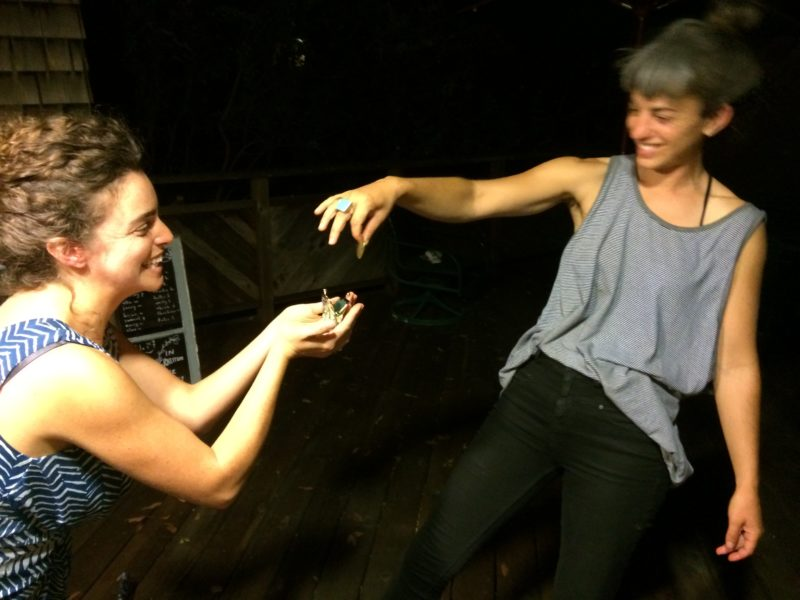 One person drops a small, unidentifiable object into the waiting hands of another person. Both people are smiling. It is dark in the background.