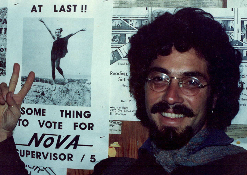 Aaron Shurin on Castro Street, in front of a poster of Silvana Nova which he helped create, ca. 1977.