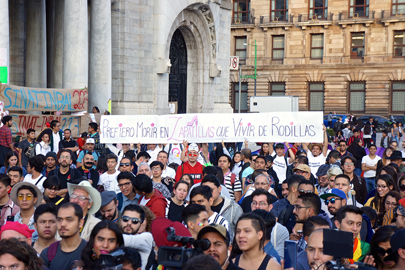 """A sign with an altered version of an Emiliano Zapata quote [translation: """"I'd rather die in my heels than live on my knees""""] flies over the December 13, 2019 counter-protest in support of Fabián Cháirez. Photo: Antonio Bertrán."""