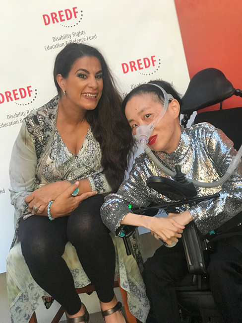 Photo of Maysoon Zayid, a Palestinian American woman with long black hair swept to one side, wearing a print top and black leggings, with Alice Wong, an Asian American woman in a wheelchair with a silver sequined top and a mask over her nose attached to a tube. Behind them is a white backdrop with the DREDF logo.
