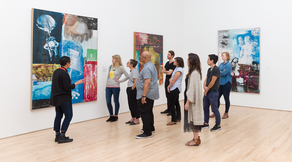 A tour group in front of a large Robert Rauschenberg silkscreened painting