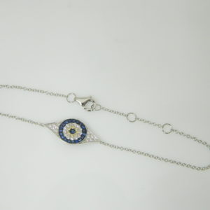 14 Karat White Gold Straight Line Mounted 6-7'' Eye Bracelet with 27 Round Cut Blue Sapphires weighing 0.21ct and 25 Round Cut Diamonds weighing 0.17ct tw.