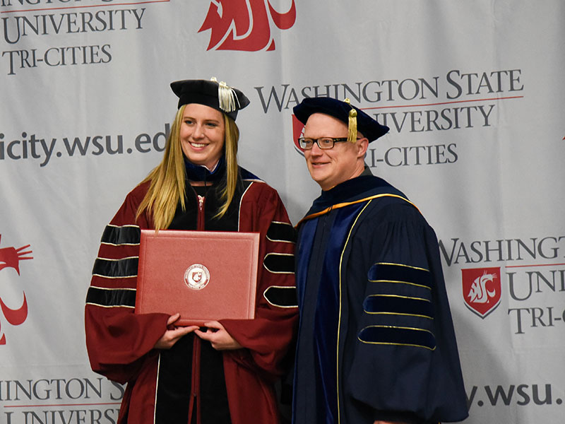 A graduate student receiving her diploma standing with professor