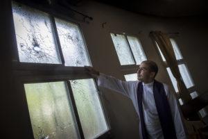 El padre Erick Alvarado, vicario de la parroquia Jesús de la Divina Misericordia, muestra los destrozos y los impactos de balas de grueso y mediano calibre.