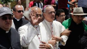 """La Iglesia católica de Nicaragua, con sus obispos a la cabeza, se volvió protagonista durante el desarrollo de la crisis. Primero, como organizadores y mediadores en el Diálogo Nacional, y luego intercediendo en los lugares de conflicto para que no hubiera más muertos y apresados. Por su labor, sin embargo, la Iglesia comenzó a ser reprimida y perseguida por el régimen, quien la culpó de ponerse del lado de la rebelión cívica que ellos calificaron como """"golpe de Estado"""". En la fotografía, el cardenal Leopoldo Brenes y monseñor Silvio Báez junto a otros obispos y el nuncio apostólico mientras llegan a la asediada Basílica San Sebastián, de Diriamba."""