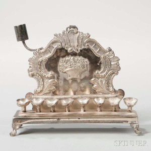 Small Polish Silverplated Hanukkah Lamp, Warsaw, late 19th century (Lot 1020). The form is elegant with mix of Rococo c-scrolls and rocaille and a Neoclassical basket of fruit, the oil pans are of minimalist design.