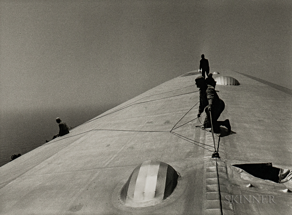 Alfred Eisenstaedt (American, 1898-1995)  Repairing the Hull of the Graf Zeppelin During the Flight over the Atlantic, 1934 (Lot 98, Estimate $3,000-5,000)