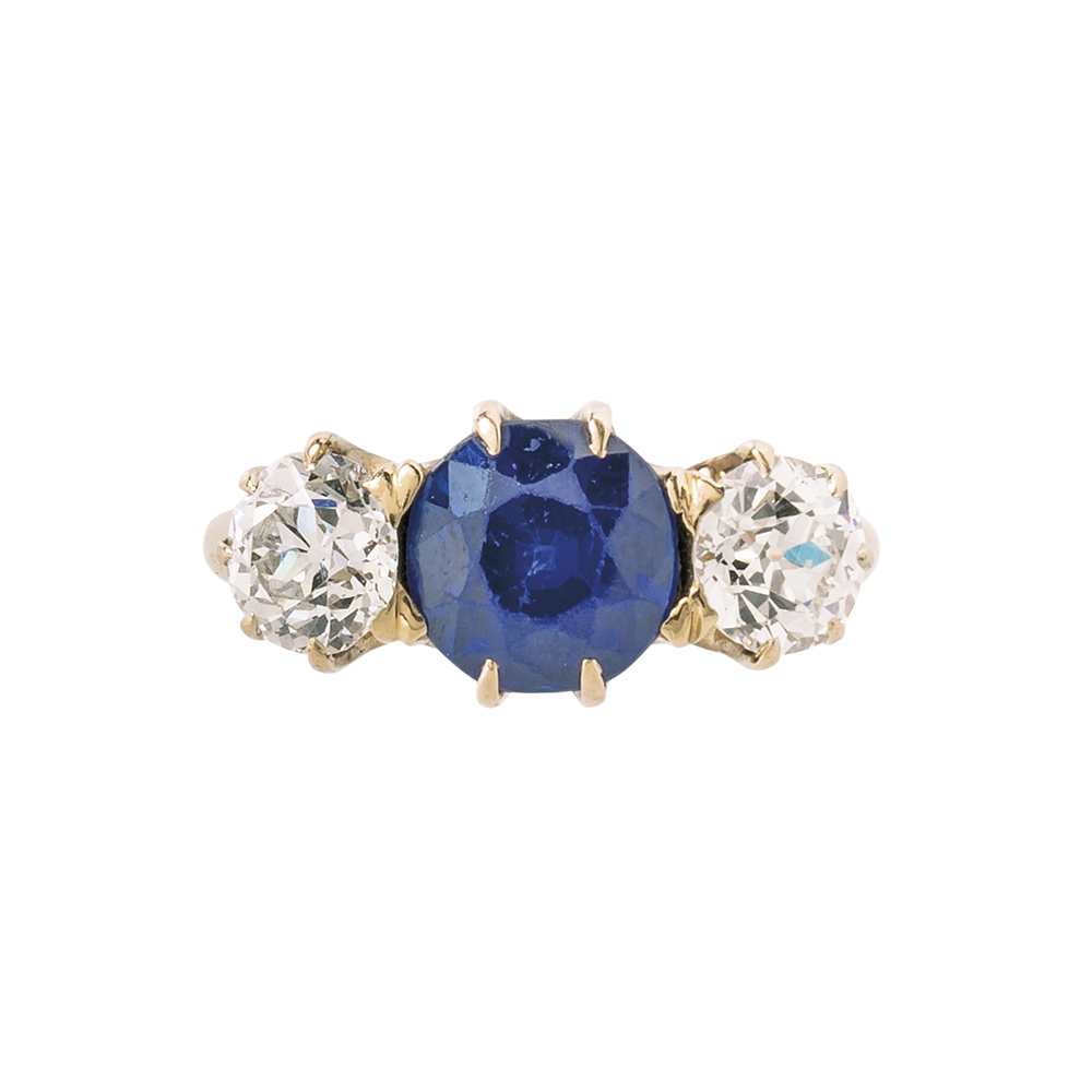 Sapphire ring with old European-cut diamonds on either side, set in a gold mount.