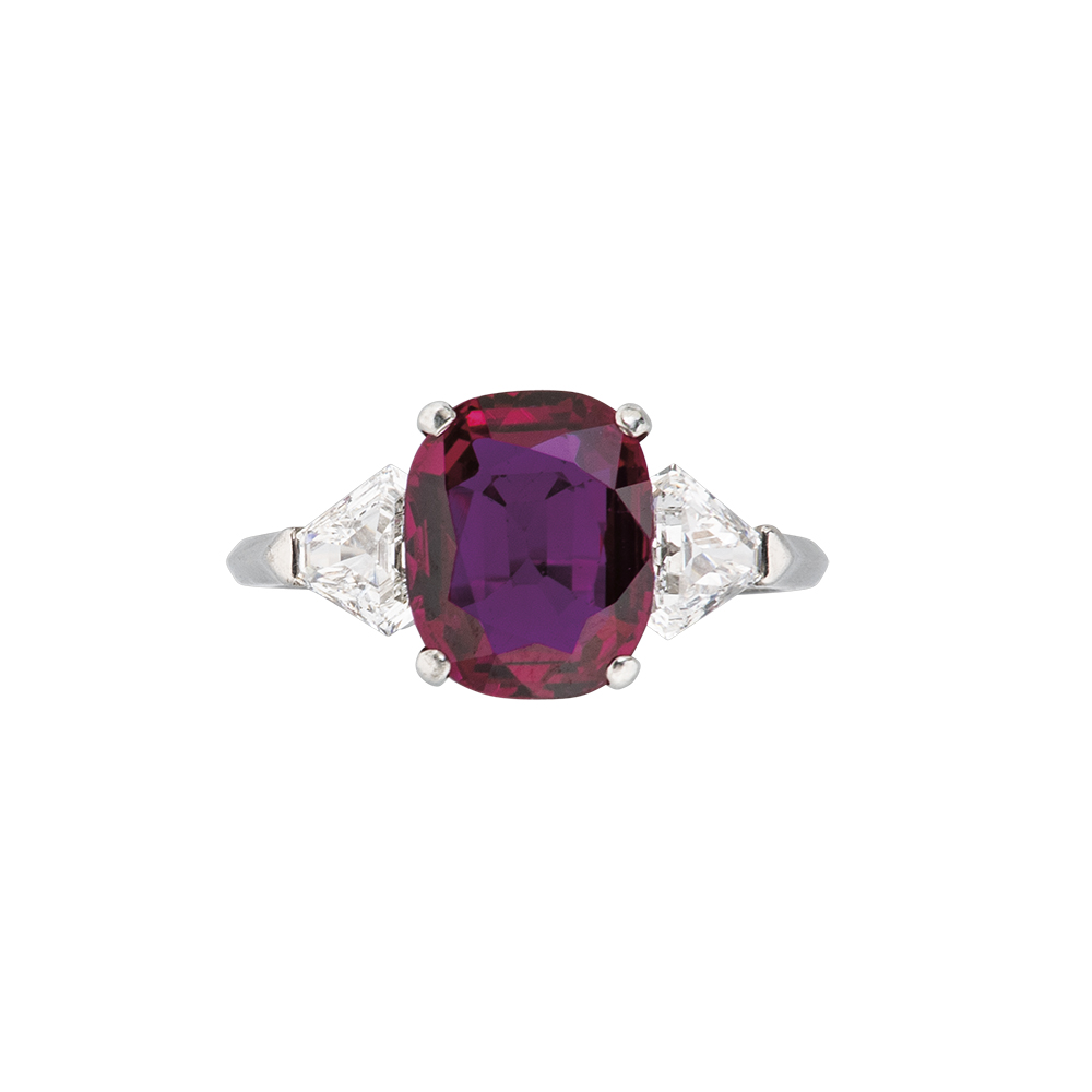 Van Cleef & Arpels cushion-cut Ruby ring with shield-shape diamond on either side. Set in platinum.