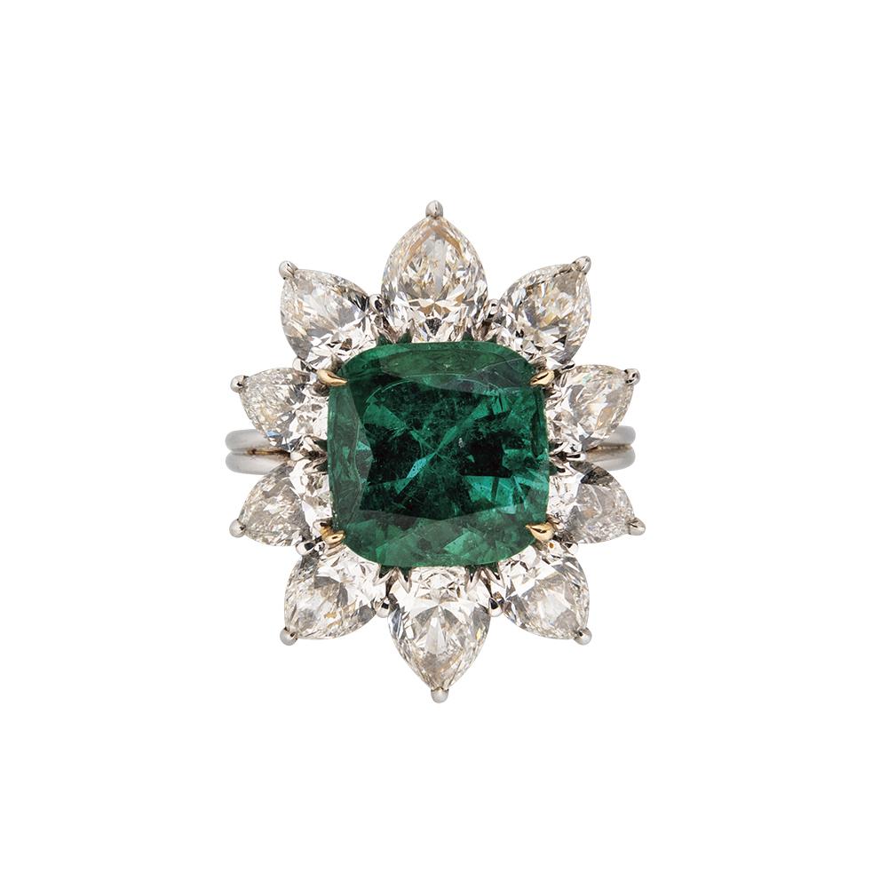 Cushion-cut emerald framed by 10 pear-shape diamonds, set in a gold ring.