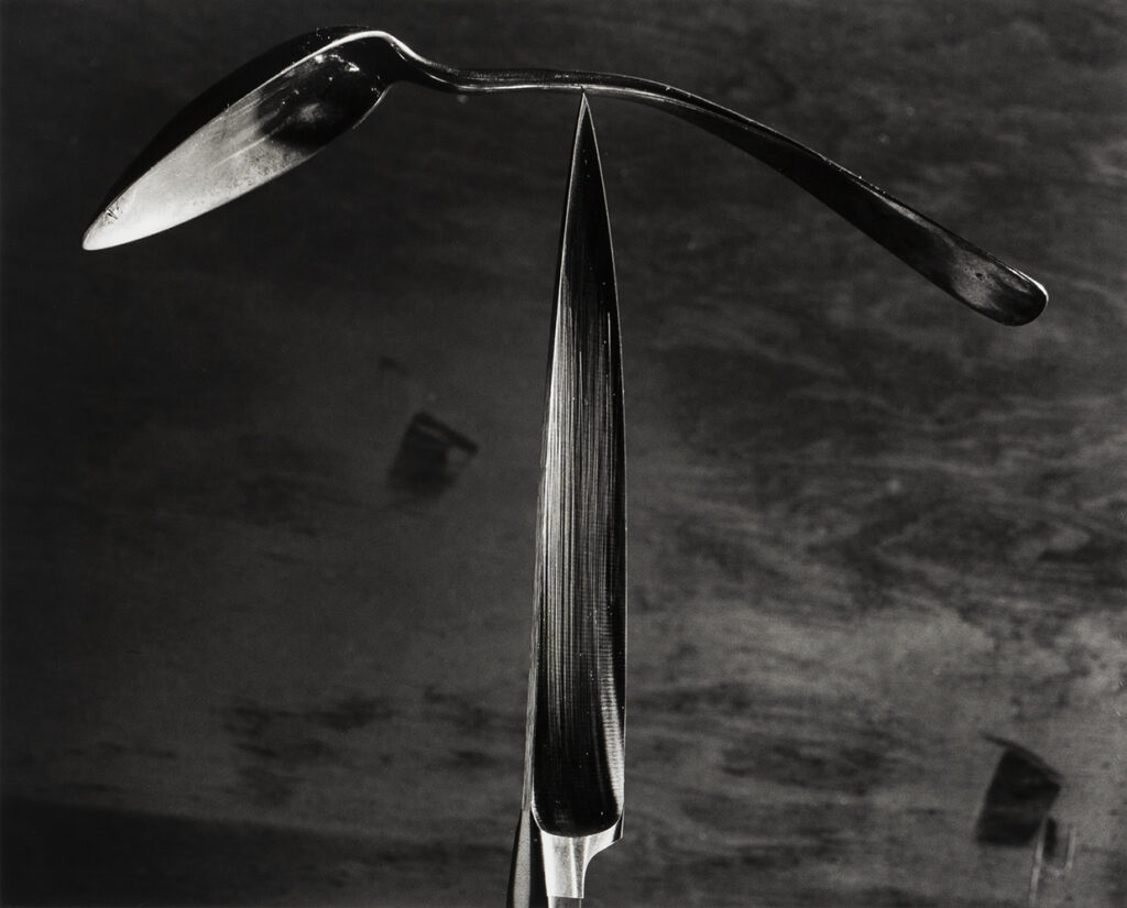 Abe Morell's photograph Knife and Spoon showing a bent spoon balancing on a standing knife.