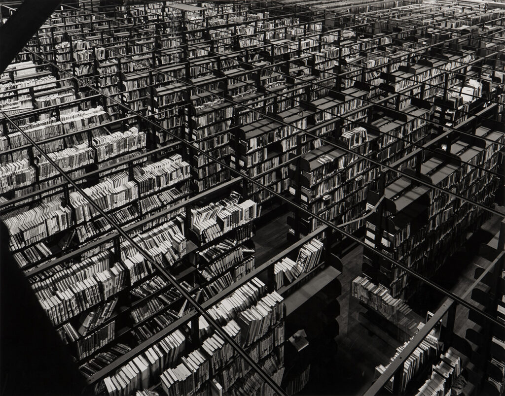 Abe Morell's photograph Bookstacks in a Very Large Space. Pictured is large room of  bookstacks from a bird's eye view.