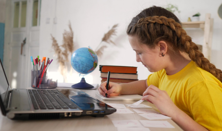 girl writing on notepad in front of laptop during online tutoring school