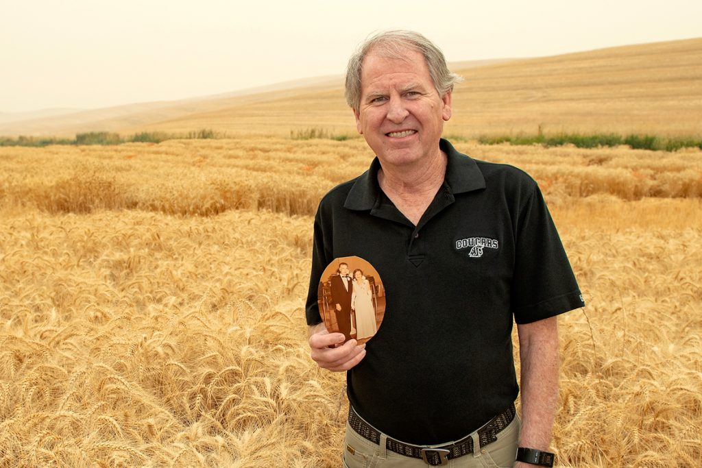 Tim Murray in wheat field holding a photo of his grandparents.