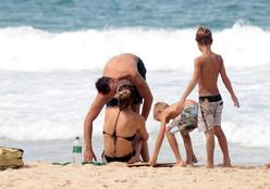 Fernanda Lima e Rodrigo Hilbert trocam beijos em praia do Rio